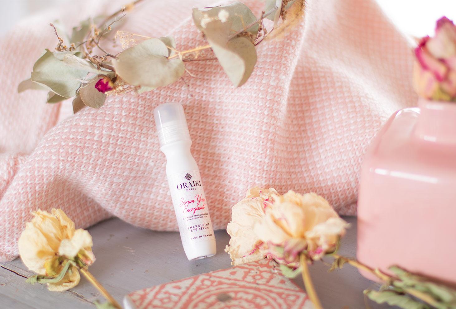 Le sérum énergisant pour les yeux de la marque Oraiki posé sur un plaid rose au milieu de fleurs sèches, sur une table grise vintage