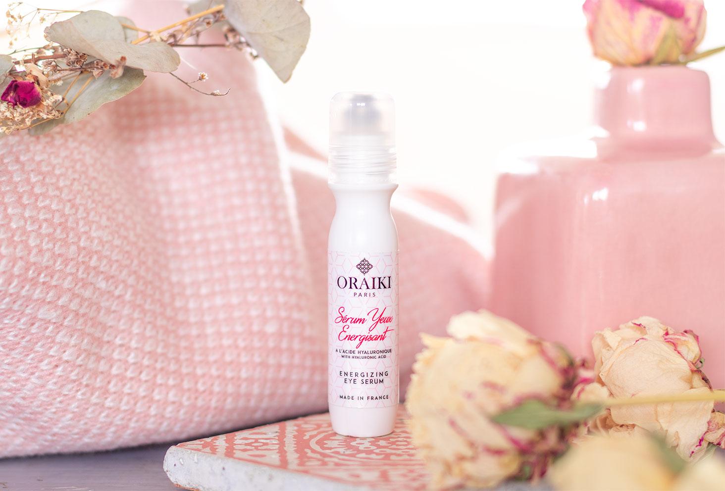 Le sérum énergisant pour les yeux Oraiki posé sur un carreaux de ciment dans un ambiance de salle de bain rose