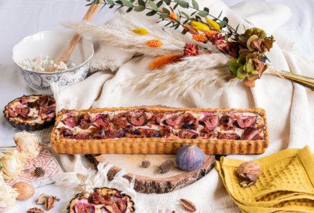 La recette de la tarte sucrée salée aux figues et au jambon, posée sur une planche en bois au milieu d'un décor d'automne