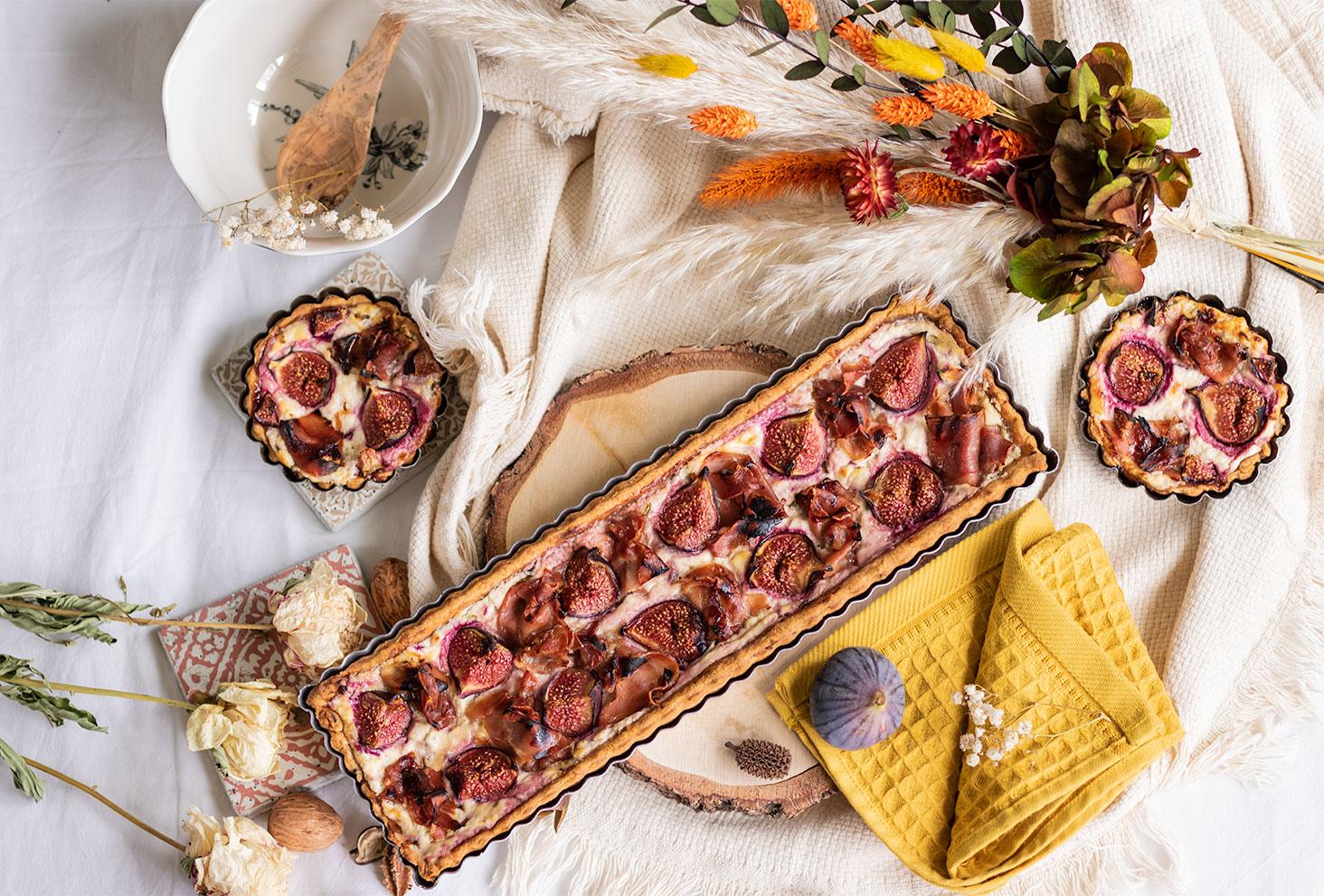 La tarte aux figues, jambon et chèvre frais, parfaite pour l'automne, posé sur un rondin de bois vue de haut dans un décor d'automne
