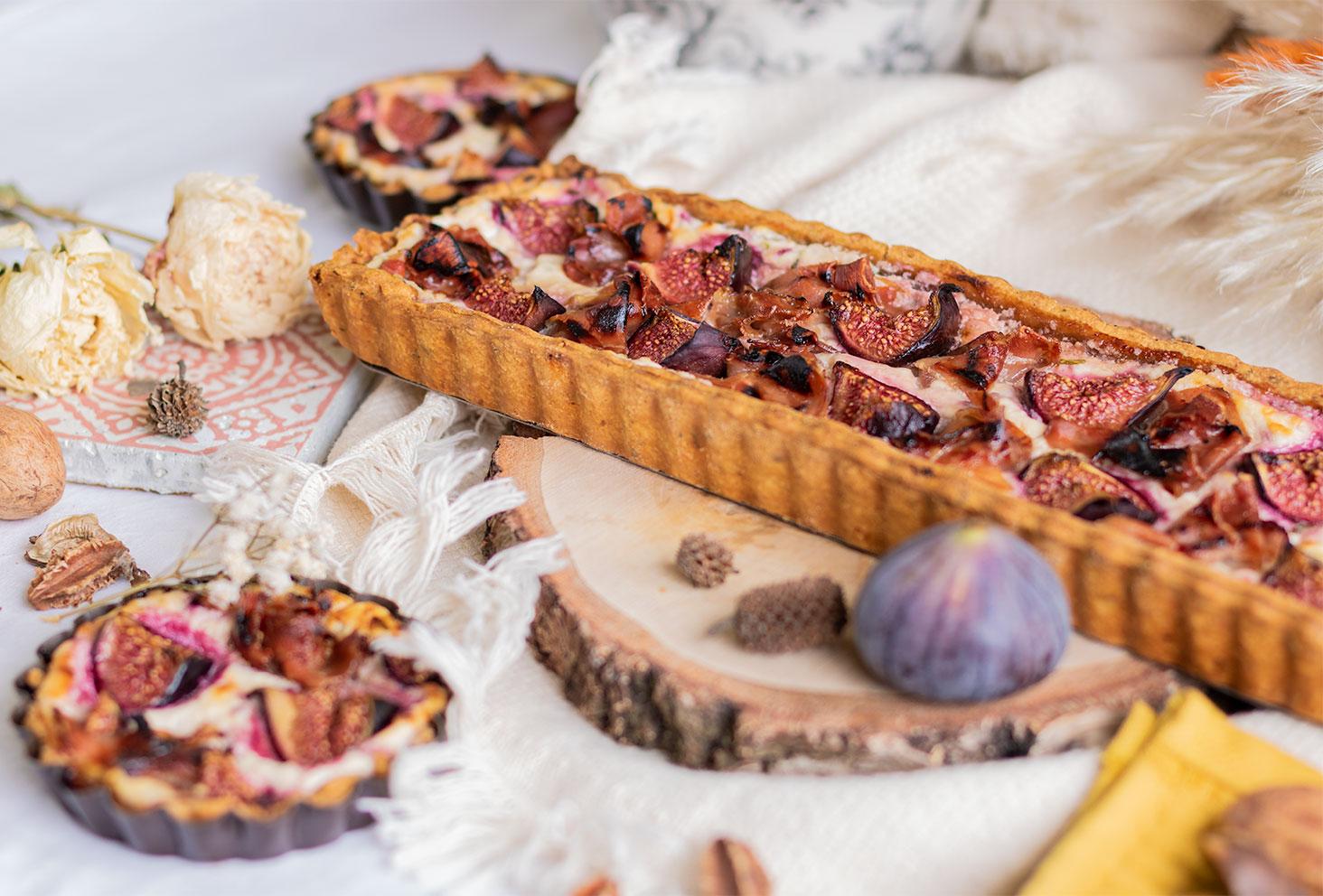Zoom sur la tarte aux figues, chèvre et jambon sec, au milieu d'un décor d'automne, sur un rondin de bois