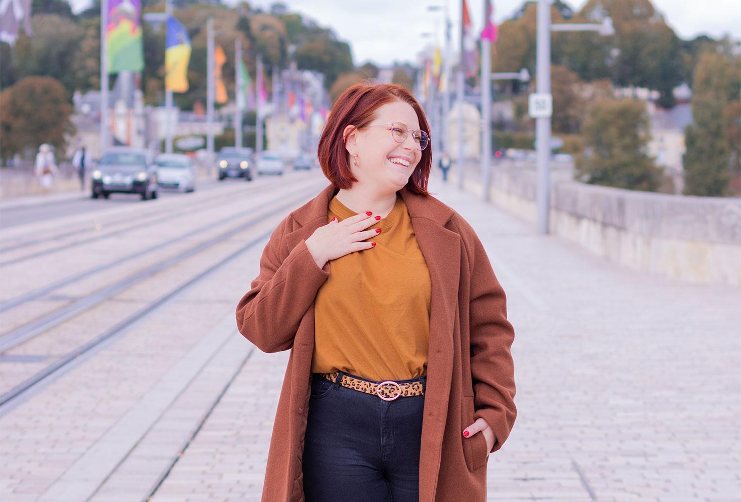 Au milieu d'un pont en look de working girl, du vernie rouge sur les ongles avec le sourire, un t-shirt camel et un manteau long marron sur les épaules