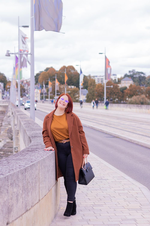 Appuyée le long du mur en pierre d'un pont au dessus de l'eau, avec le sourire, en talons et manteau marron long