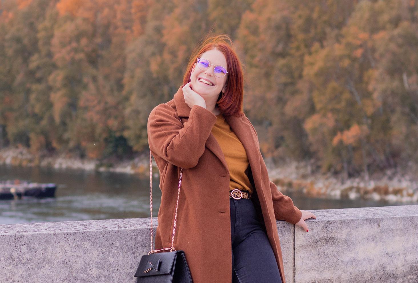 Appuyée le long du mur en pierre d'un pont au dessus de l'eau, avec le sourire, une main sur le visage en manteau marron long Bizzbee