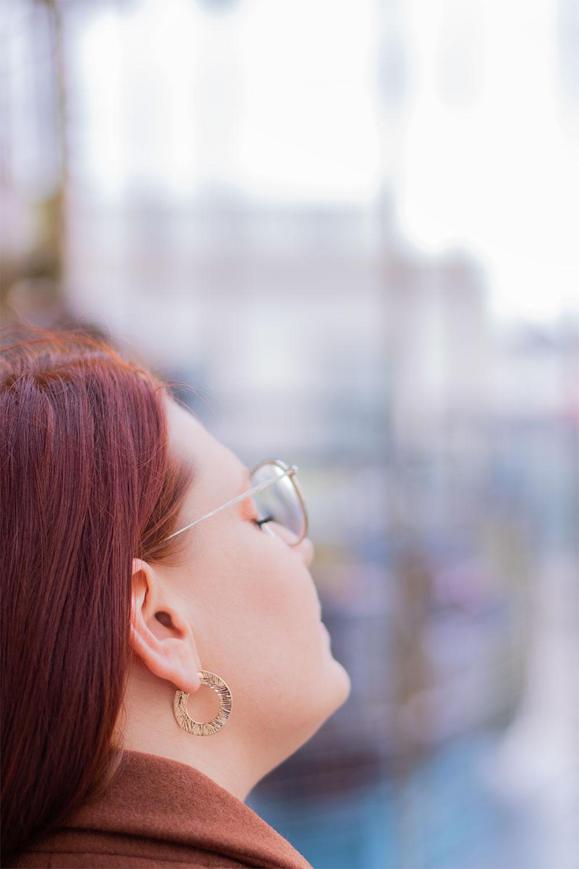 Zoom de côté sur les boucles d'oreilles rondes et dorées MOA portées