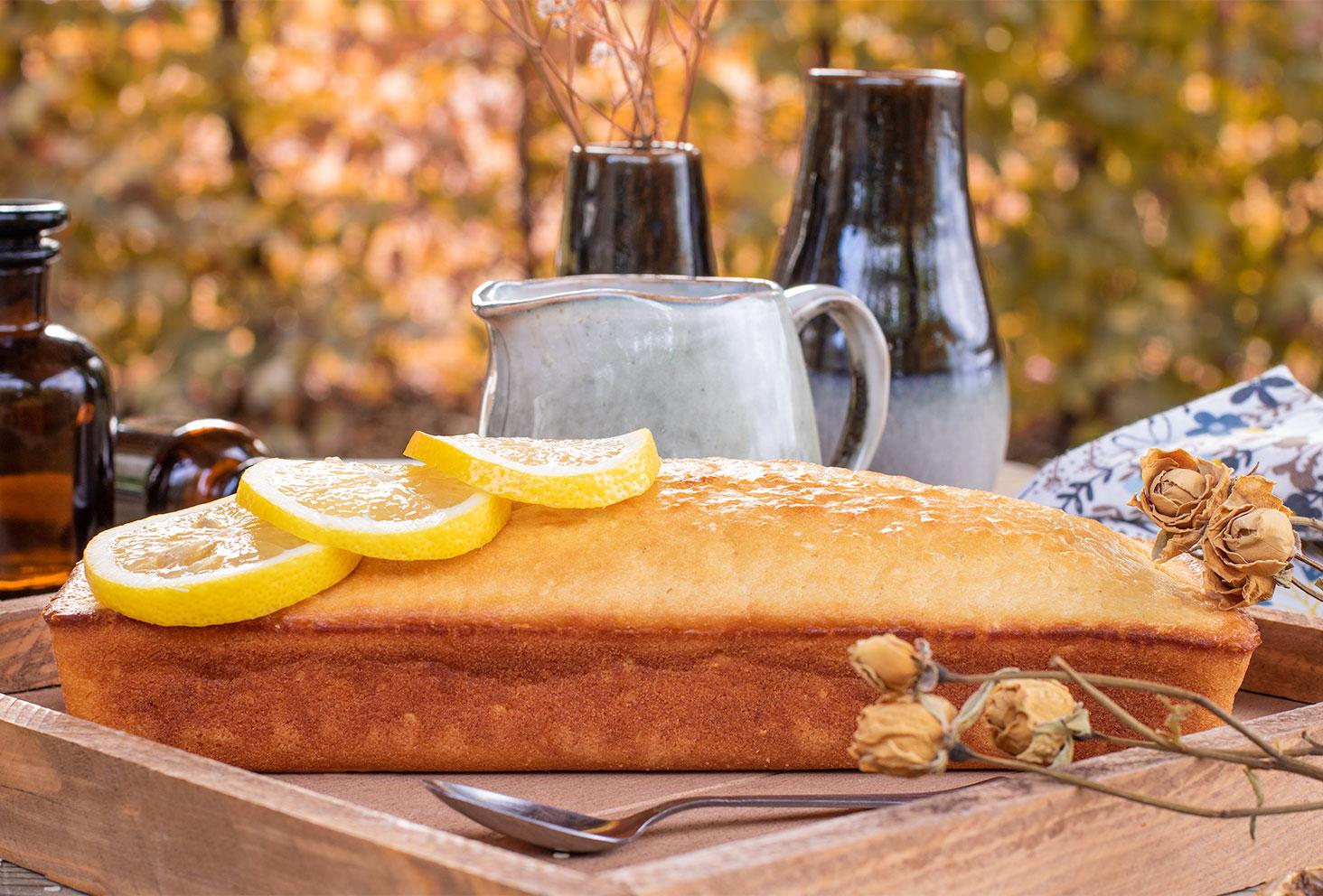 Zoom sur un cake au citron moelleux posé sur un plateau en bois pour le goûter