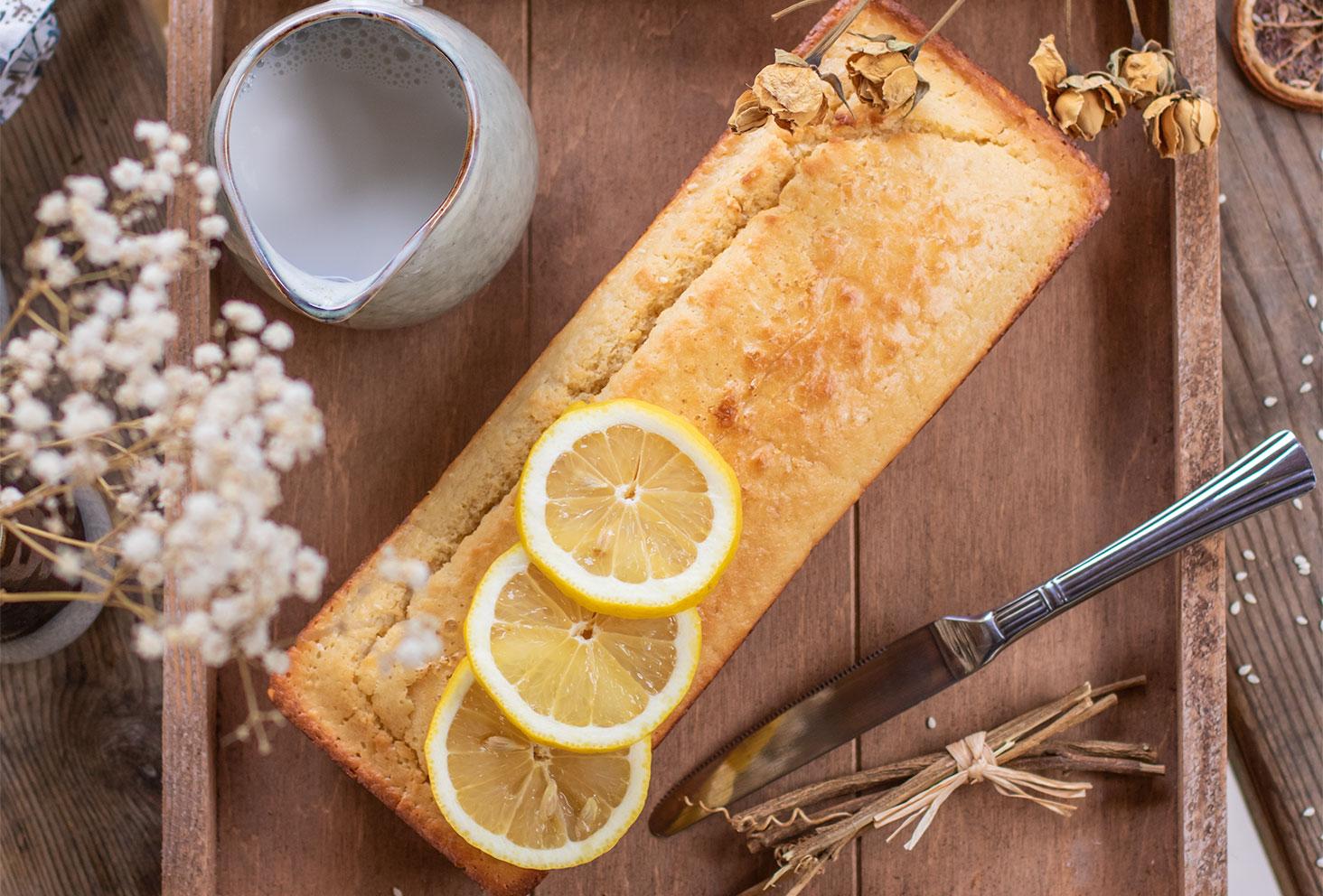 Zoom sur un cake au citron posé sur un plateau en bois, vu de haut à côté d'un pot à lait d'amande