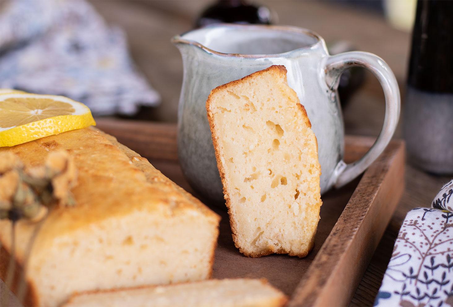 Zoom sur une part de cake au citron et graines de sésame, posé sur un plateau en bois le long d'un pot à lait