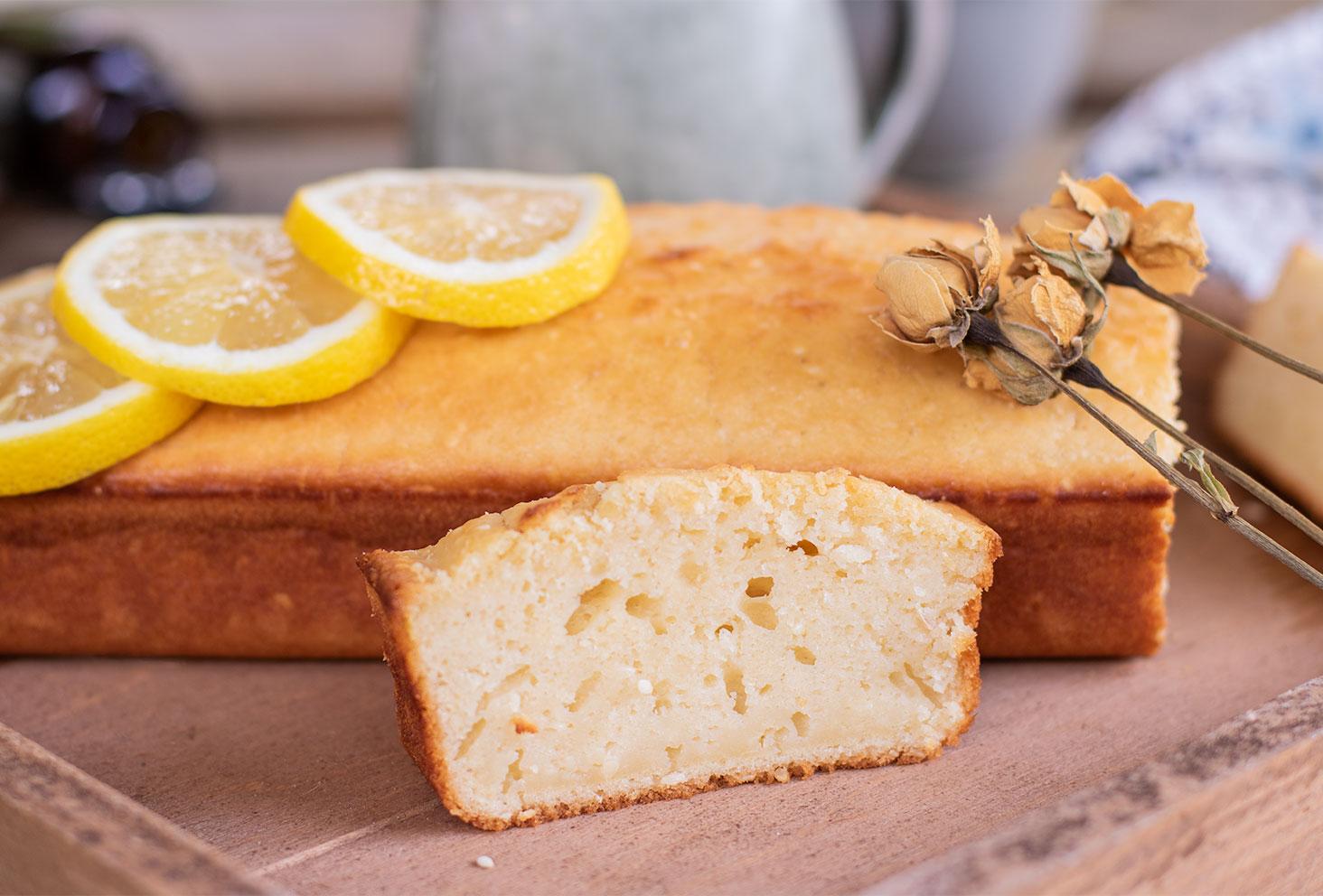 Zoom sur une part de lemon cake moelleux posé sur un plateau en bois devant le cake entier
