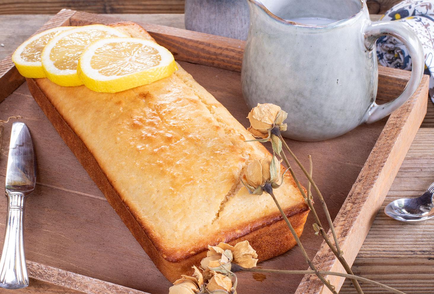 Un cake au citron sur un plateau en bois au milieu de fleurs séchées jaunes pour le goûter