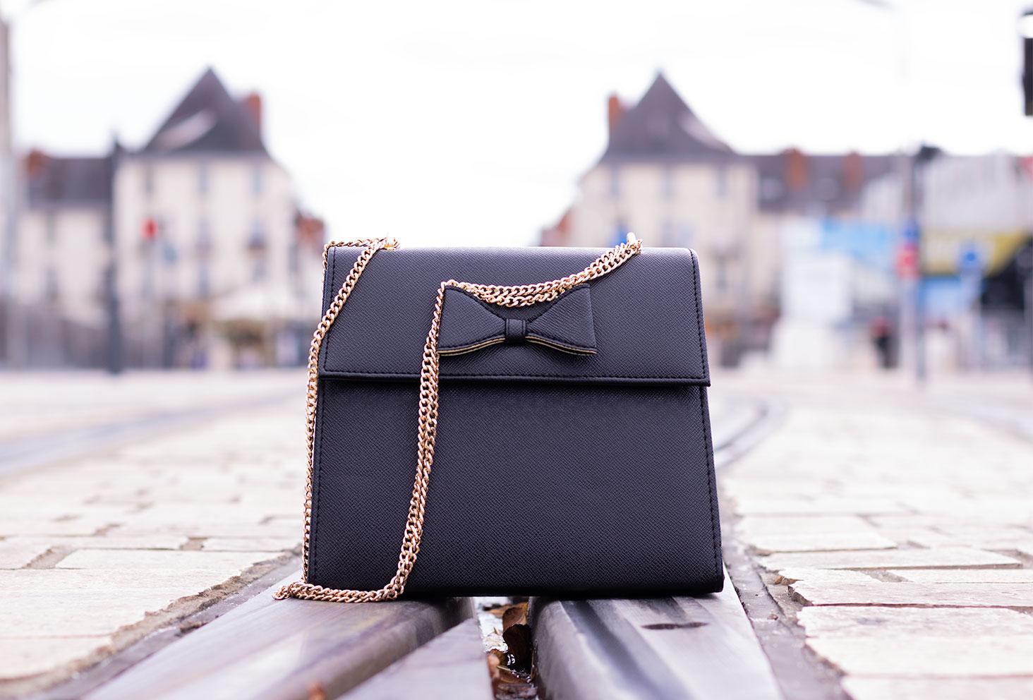 Zoom sur le sac noir rigide avec un noeud sur le dessus, posé par terre au milieu d'une rue en plein centre ville