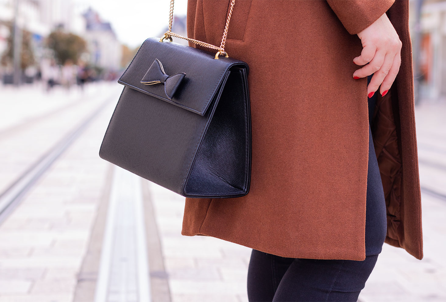 Zoom sur le sac noir rigide avec un noeud sur le dessus, porté avec un manteau marron