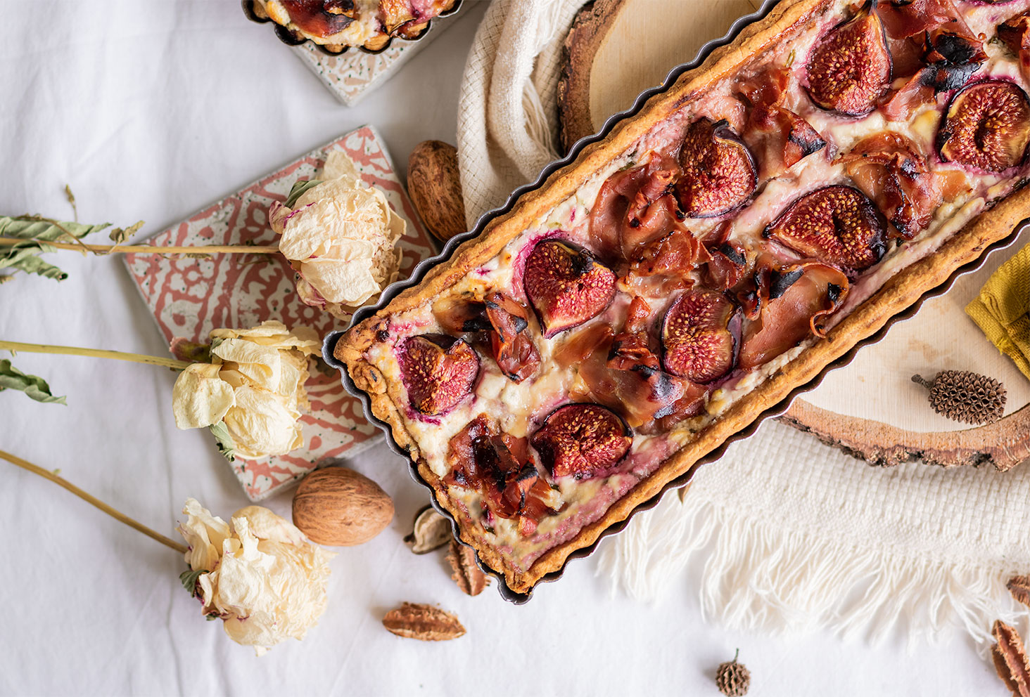 Zoom sur la tarte cuite aux figues, jambon, chèvre et miel, posée sur un rondin de bois au milieu d'un décor d'automne