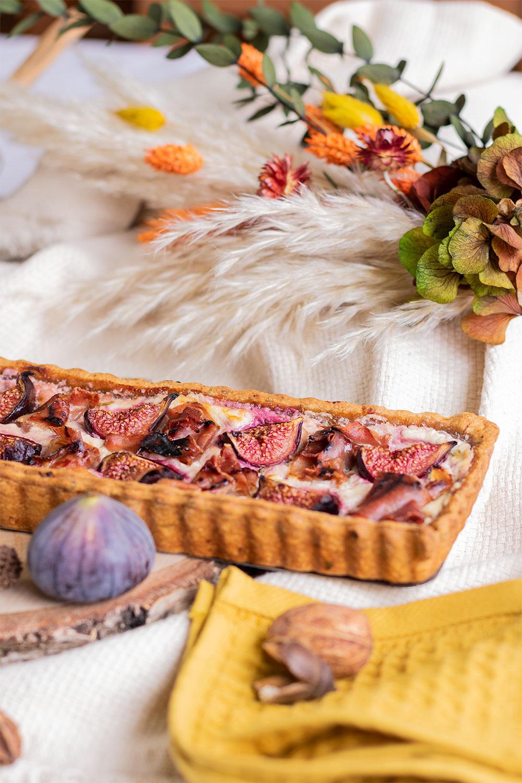 Zoom sur le côté de la tarte rectangulaire sucrée/salée aux figues et jambon, posée sur un rondin de bois devant un bouquet de fleurs sèches