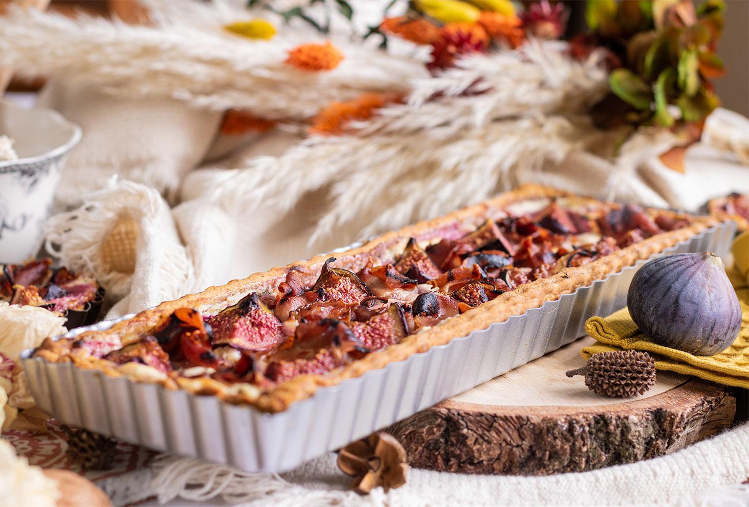 Zoom sur la tarte aux figues, chèvre et jambon, encore dans le plat à tarte en métal gris, posée sur un rondin en bois