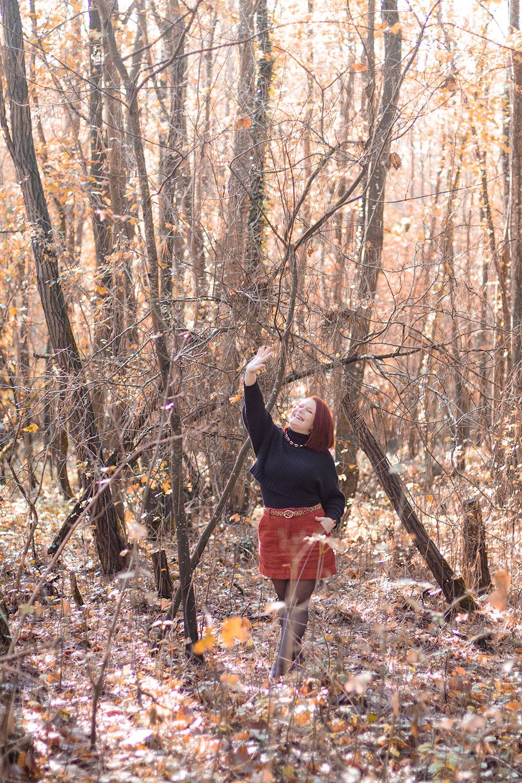 En plein milieu des bois en robe bordeaux et pull noir à col roulé, une main en l'air pour se cacher du soleil d'automne avec le sourire