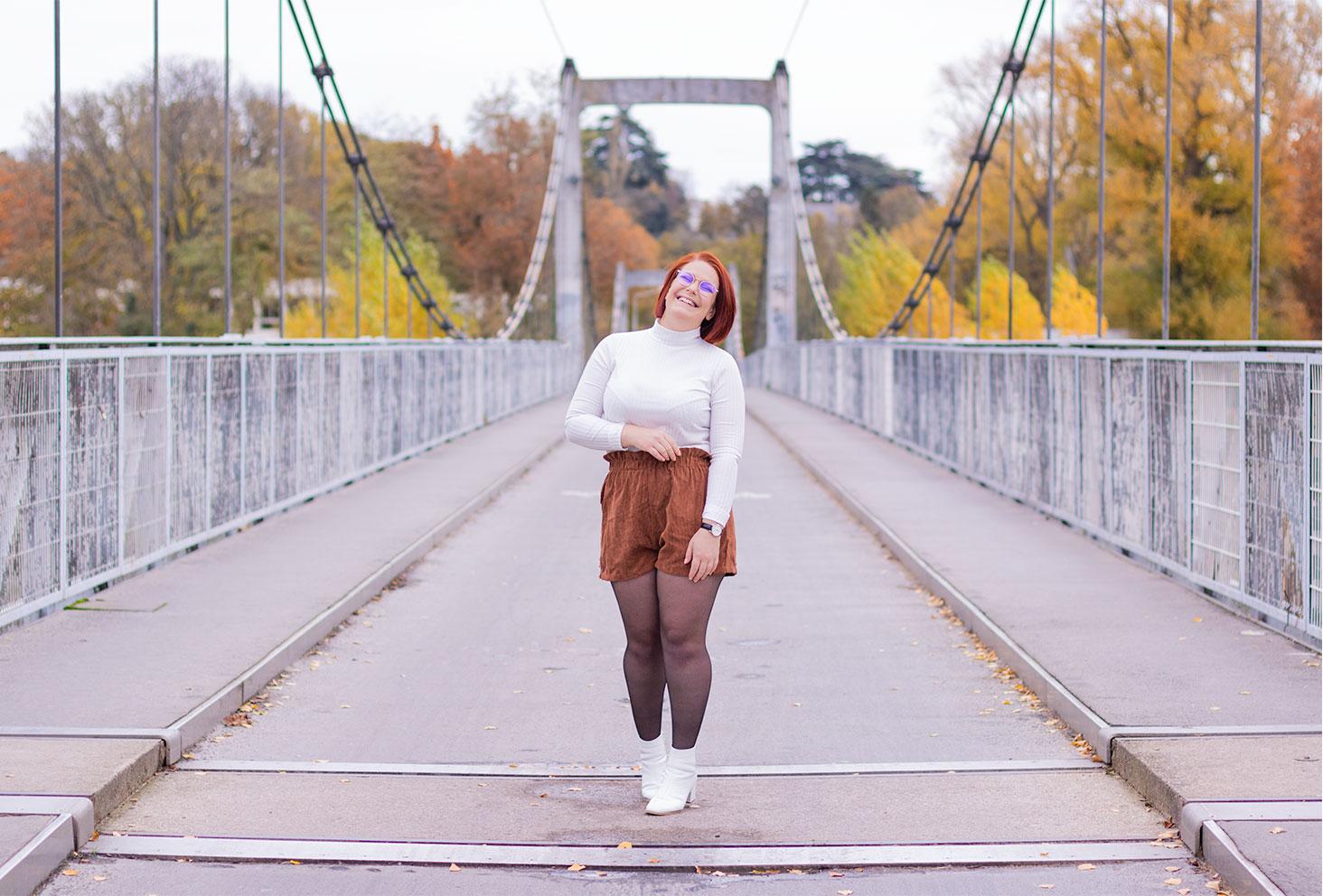 Avec le sourire au milieu d'un pont suspendu, en bottines à talons blanches et short taille haute marron, pour un look au sujet d'Instagram