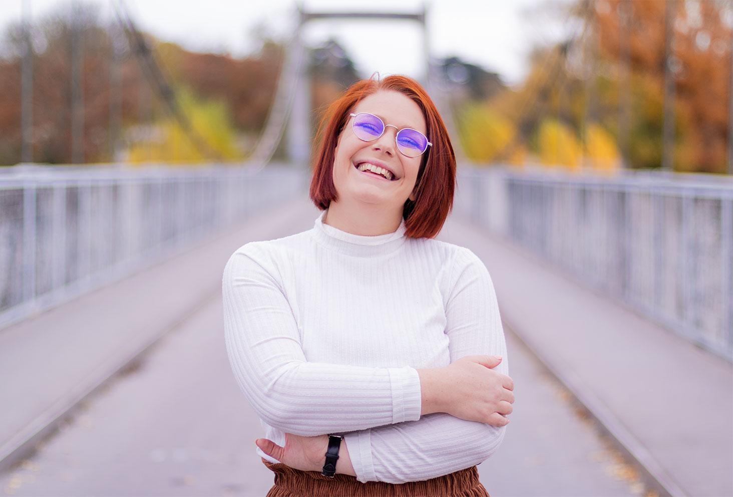 Les bras croisés devant la poitrine, avec le sourire, au milieu d'un pont de fils suspendu