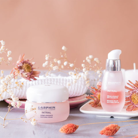 La crème apaisante et le sérum apaisant INTRAL sur une table bleutée vintage, dans un décor de salle de bain au milieu de fleurs séchées