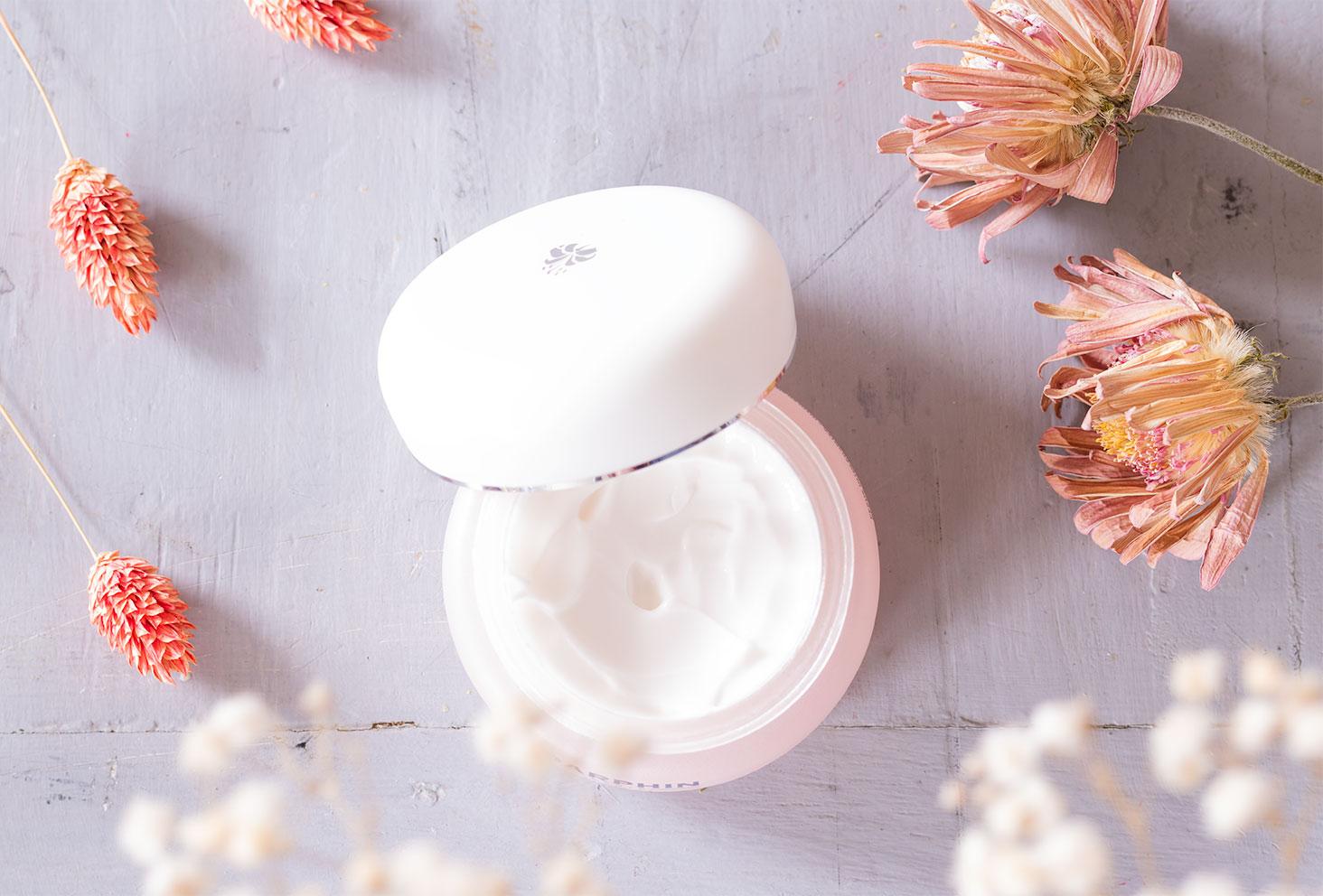 Zoom sur le pot de la crème apaisante de Darphin ouverte au milieu de fleurs séchées sur une table vintage
