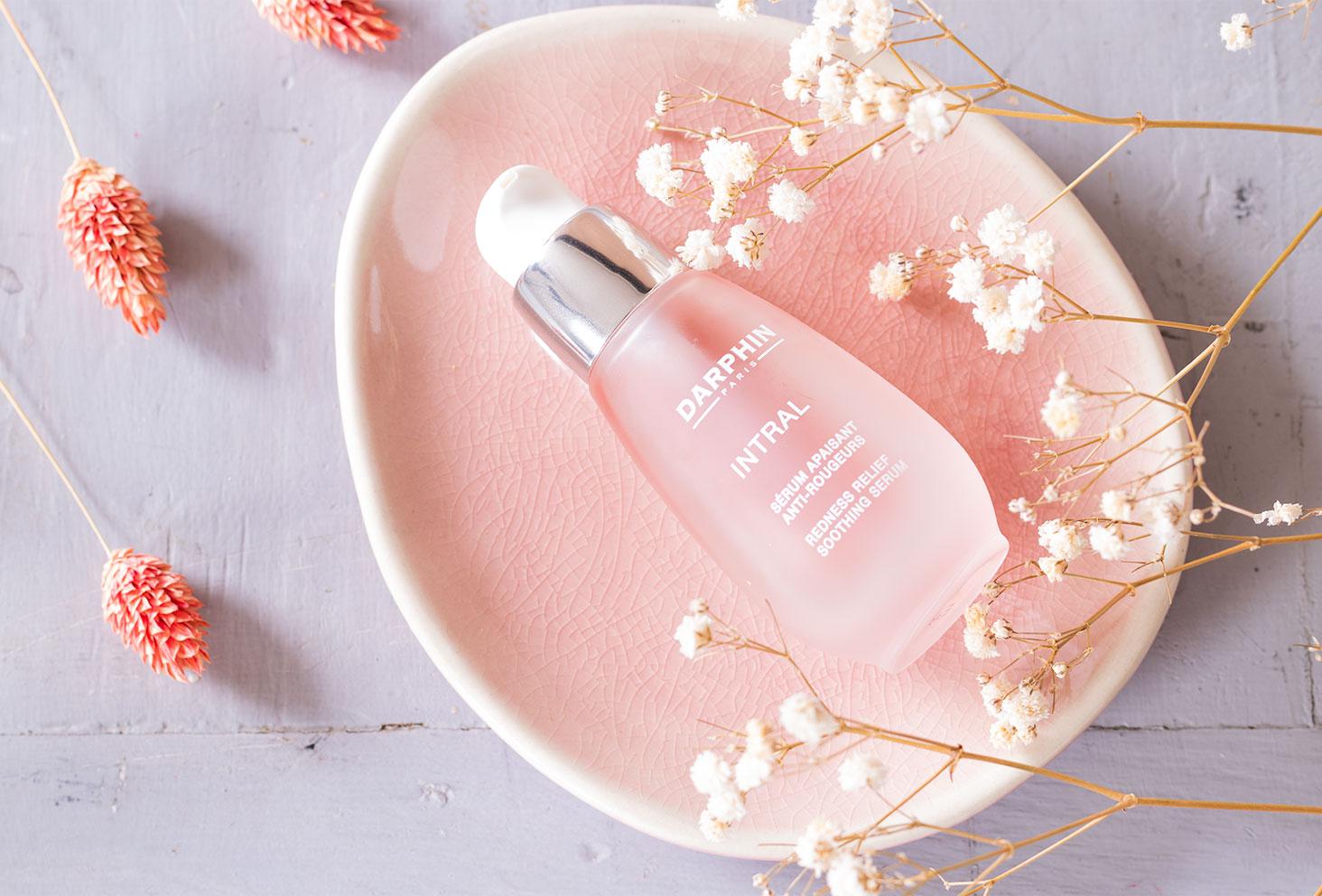 Le sérum apaisant anti-rougeurs allongée dans une coupelle rose au milieu de fleurs séchées blanches et roses