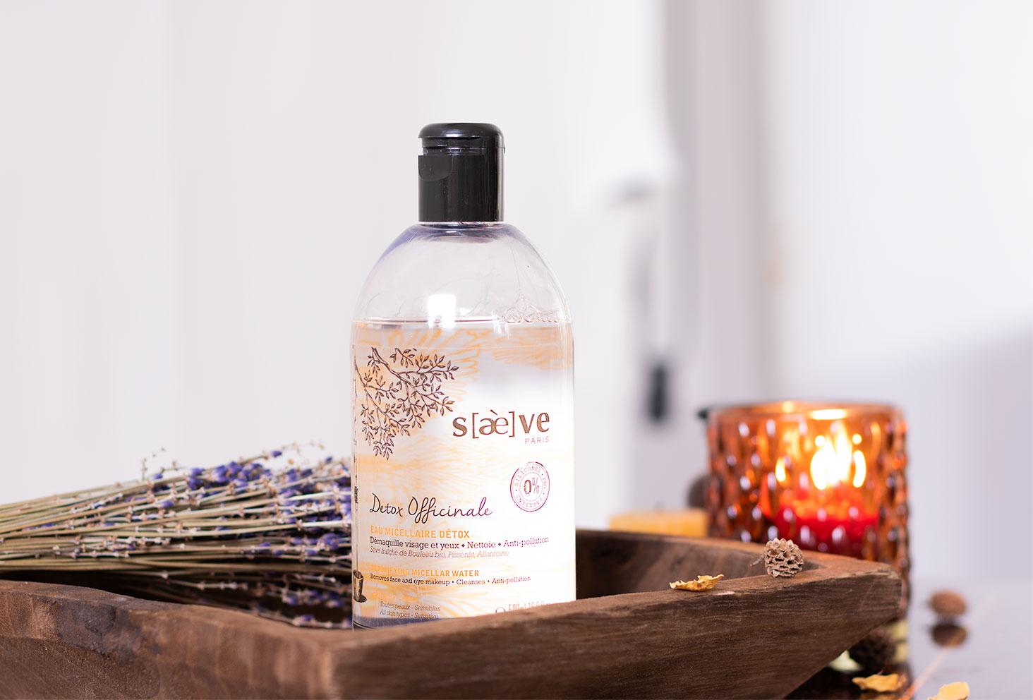 Detox Officinale l'eau micellaire démaquillante Saeve, posé dans une assiette en bois au milieu de lavande et de bougies aux couleurs de l'orient