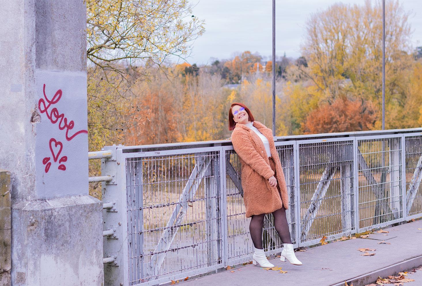 Look en manteau en fausse fourrure et bottines à talons blanches, pour un article au sujet de la disparition des likes sur Instagram avec le rappel des coeurs rouges tagué sur le mur