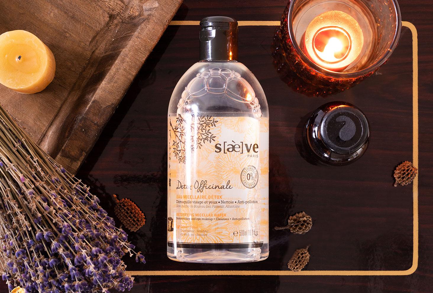 L'eau micellaire Detox Officinale de Saeve allongée sur une table foncée en bois vernis au milieu de bougies et de lavande, dans un décor reposant