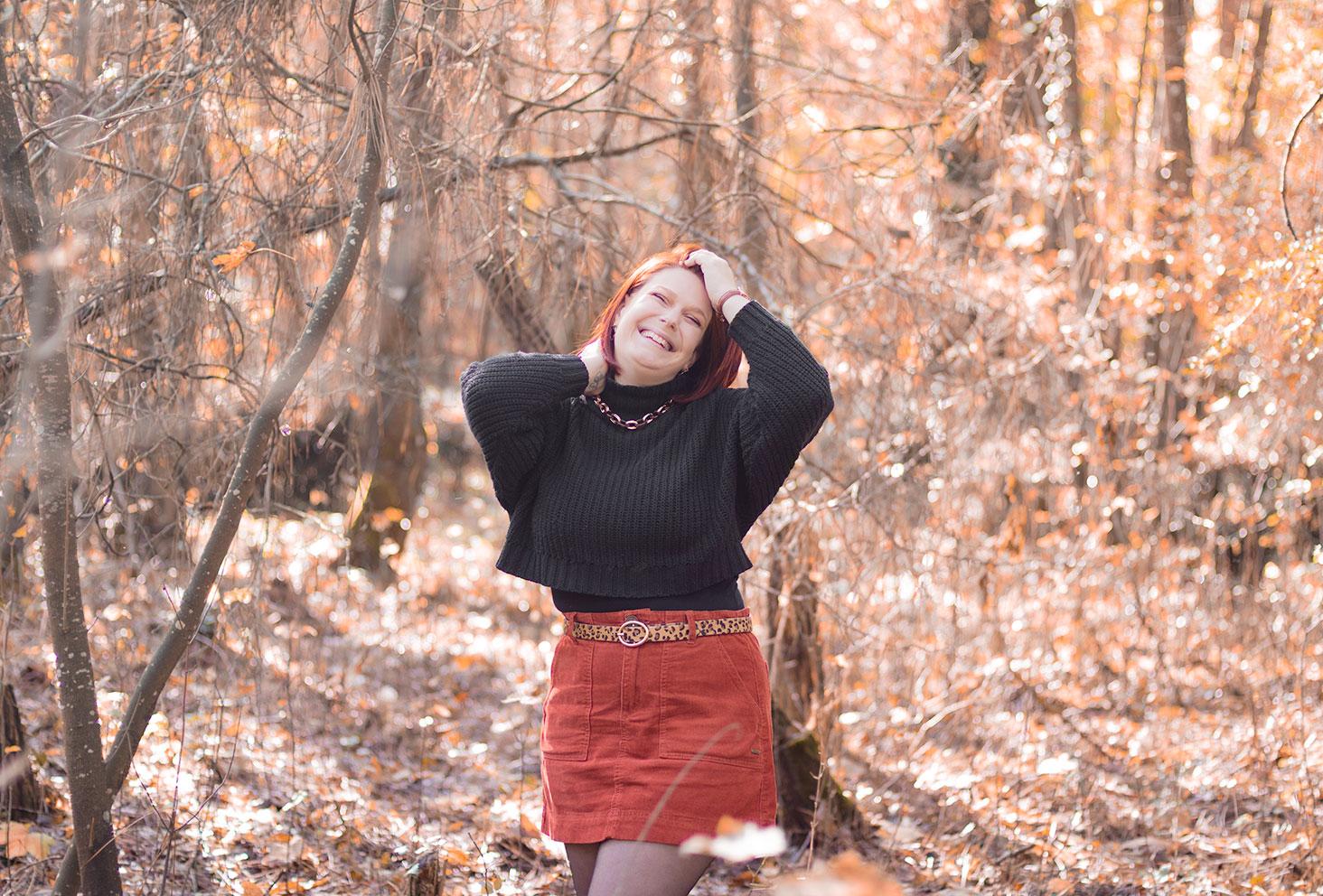 Avec le sourire et les mains dans les cheveux, au milieu des bois avec le sourire, pour un look automnal du TAG que préfères-tu