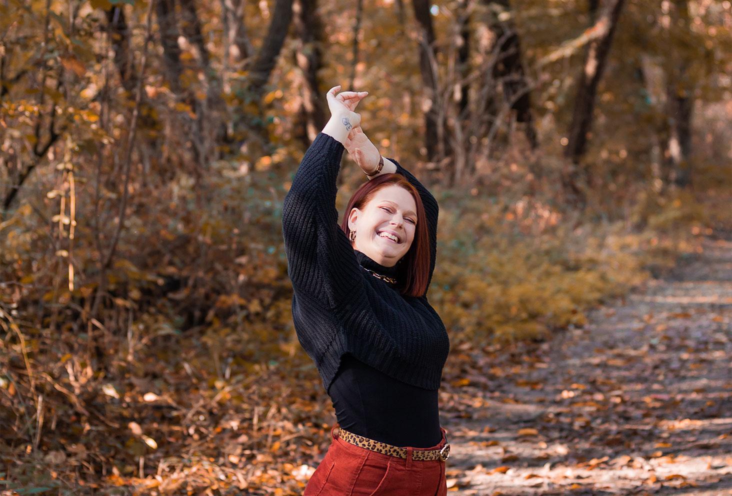 Dans la forêt avec le sourire, les mains au dessus de la tête, avec un pull court oversize à col cheminé noir