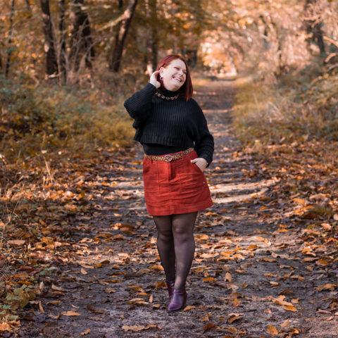 Dans la forêt dans une allée automnale, en jupe bordeaux et pull oversize noir, avec le sourire pour le TAG que préfères-tu