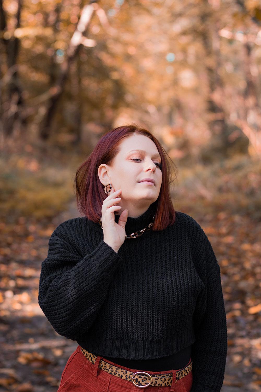 Zoom sur le pull court noir SheIn porté dans un look au milieu de la forêt, une main sur le cou sans sourire