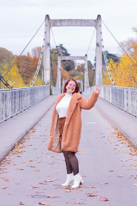 Au milieu d'un pont avec le sourire et un bras en l'air, en manteau rose à fausse fourrure SheIn