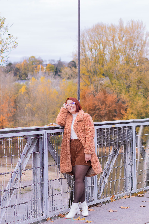 Appuyée contre la rambarde d'un pont de fils, avec le sourire, en manteau rose SheIn et bottines blanches La Halle
