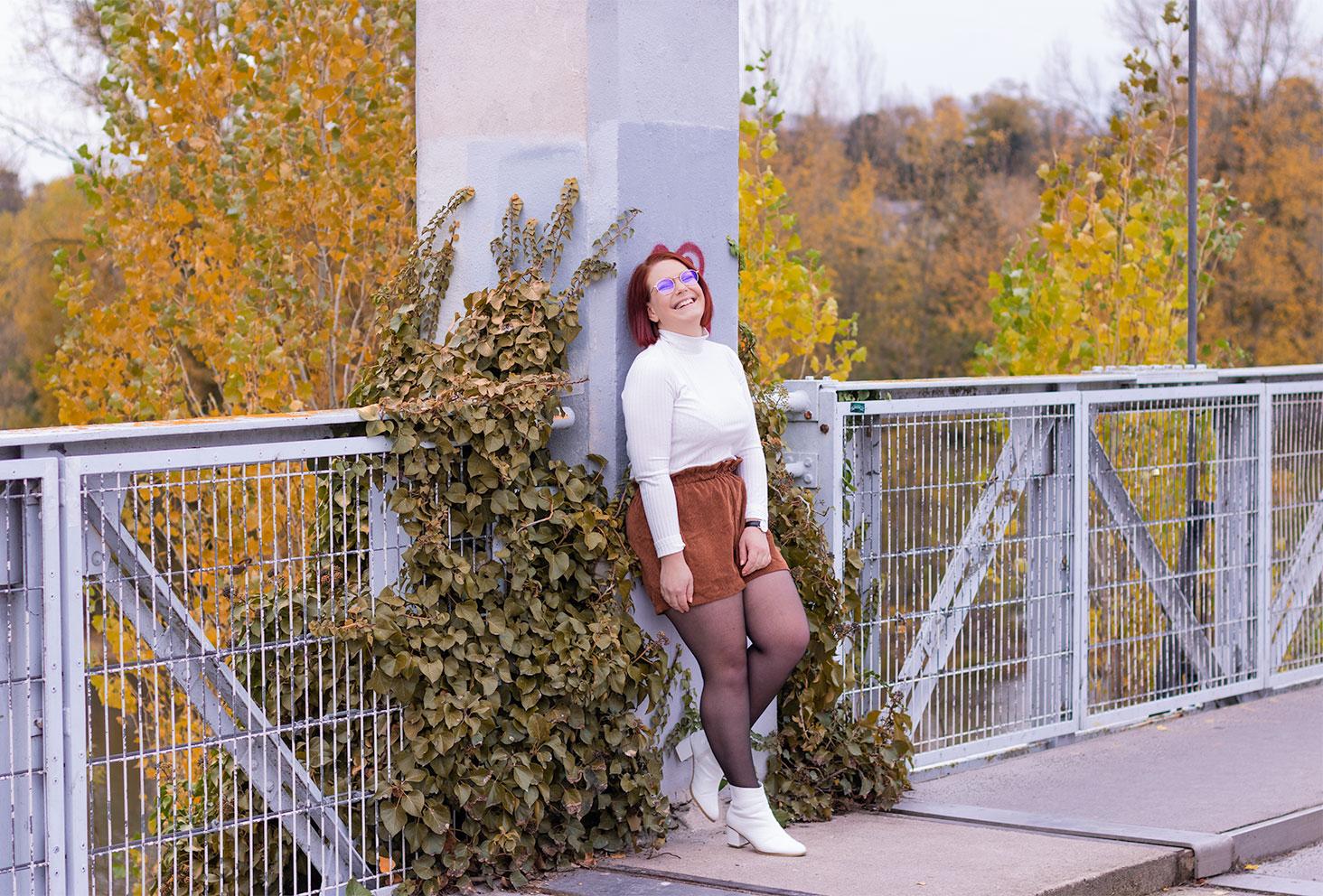 Appuyée le long d'un poteau d'un pont de fils, avec le sourire, en t-shirt blanc et short marron en velours taille haute