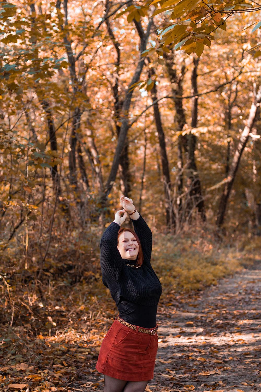 Dans les bois en jupe en velours et pull oversize avec le sourire, les mains levées au dessus de la tête