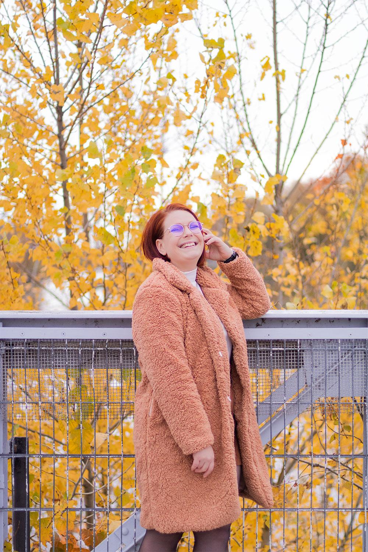 Accoudée le long des rambardes d'un pont de fils avec le sourire, en manteau rose en fausse fourrure SheIn