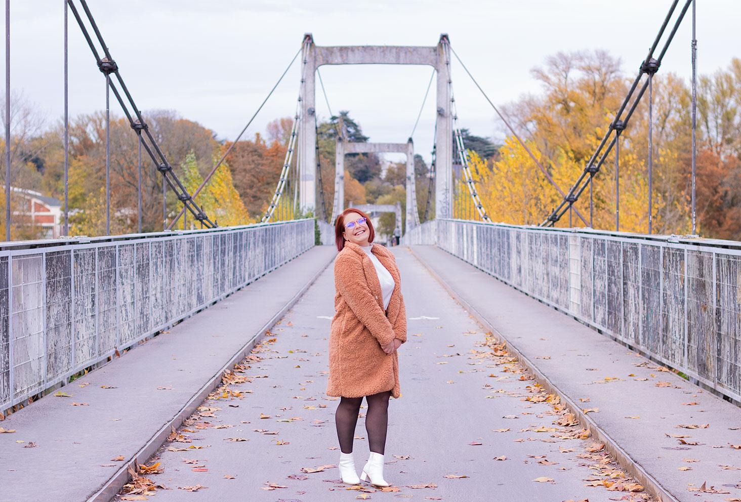 Au milieu d'un pont avec le sourire, en manteau fausse fourrure beige rosé et bottines blanches