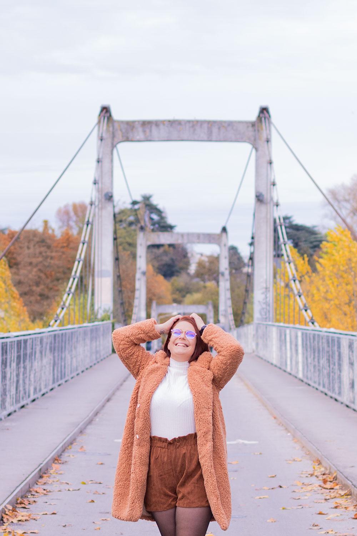 Sur un pont de fils au milieu des couleurs automnales, avec le sourire et les mains sur le haut de la tête, dans un look parfait pour l'hiver