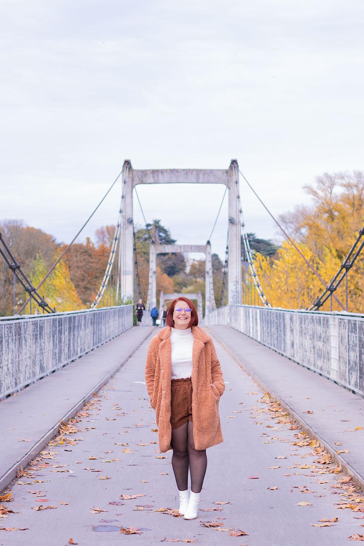 Manteau Shein et bottines blanches La Halle, les mains dans les poches, au milieu d'un pont avec le sourire