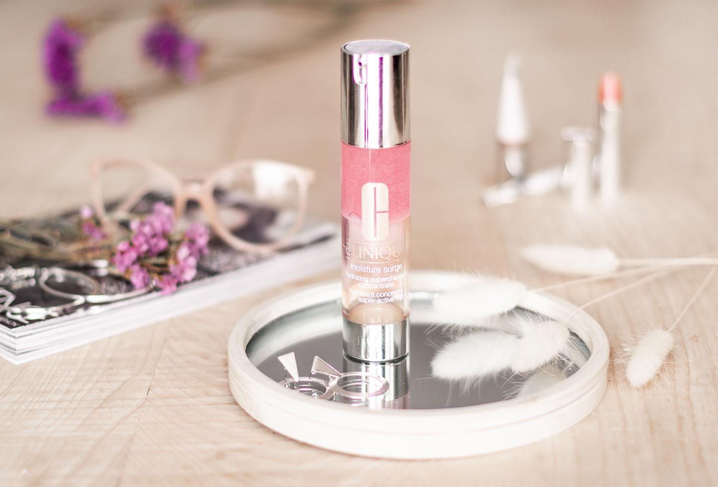 Le produit super hydratant de Clinique sur un miroir, posé sur une table en bois devant un magazine, au milieu de fleurs séchées