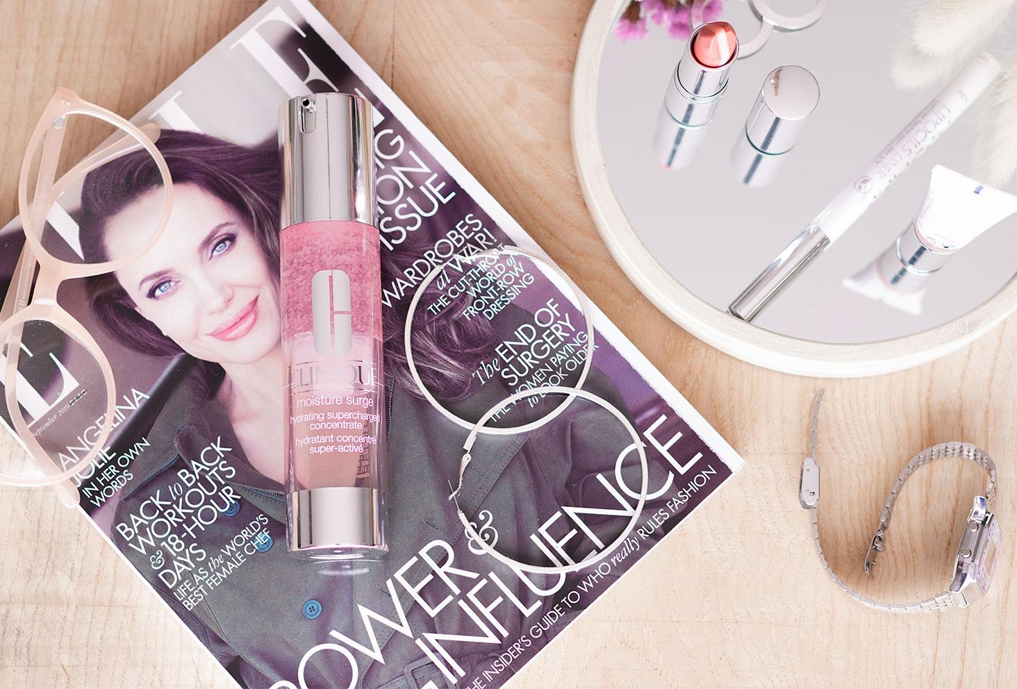 Le Moisture Surge de Clinique posé allongé sur un magazine au milieu de maquillage et de bijoux argentés