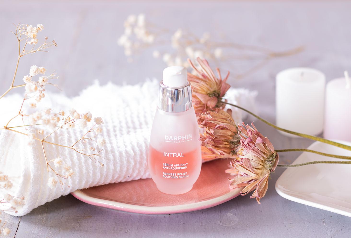 Le sérum apaisant anti-rougeurs de Darphin, dans un flacon en verre, posé dans une coupelle rose au milieu de fleurs séchées