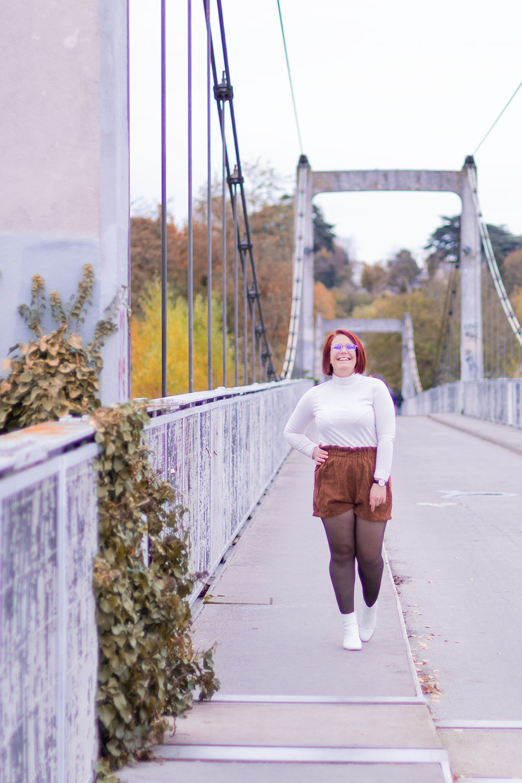 Look t-shirt blanc et short taille haute en velours, marchant sur le trottoir d'un pont, avec le sourire et une main sur la hanche
