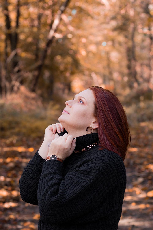 Zoom de profil sur les bijoux portés dans un look au milieu de la forêt, le regard vers le haut de profil