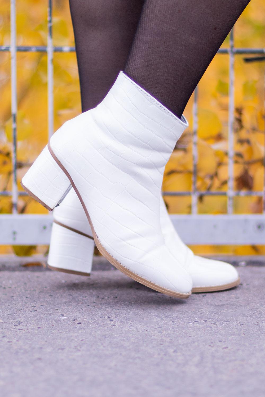 Zoom sur des bottines blanches à talons en simili cuir à motifs croco portées