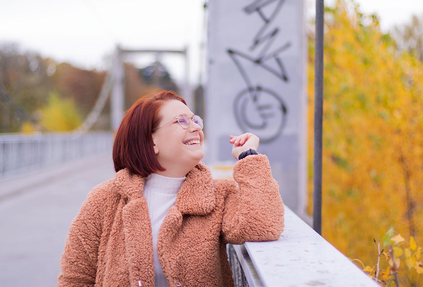 Zoom sur le col du manteau rose SheIn porté, accoudée avec le sourire à la rambarde d'un pont