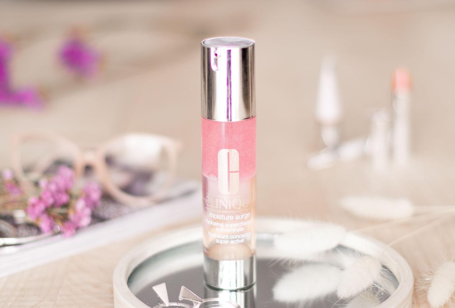 Le produit Moisture Surge de Clinique rose sur un miroir argenté