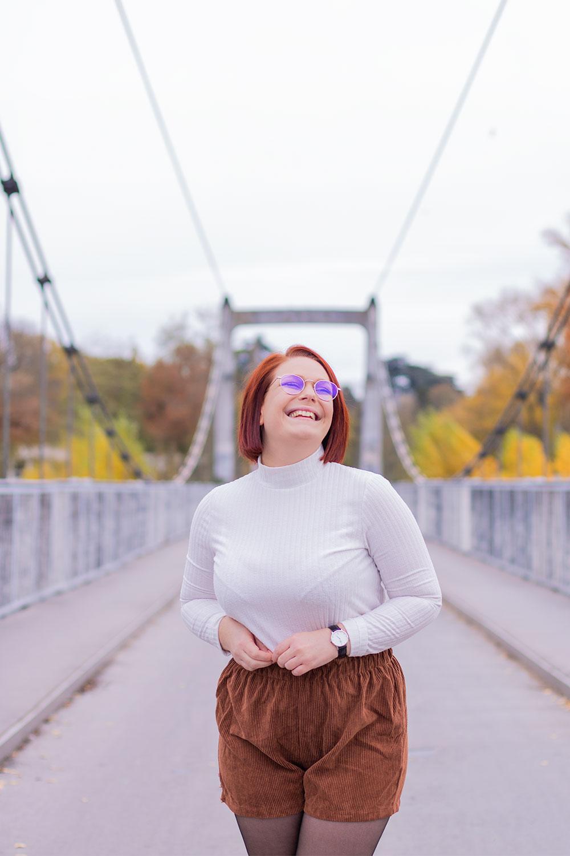 Avec le sourire au milieu sur un pont suspendu, look vintage en short taille haute en velours marron