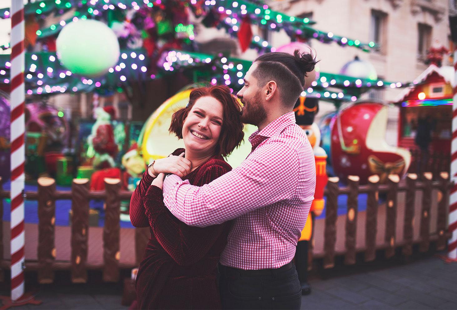 Dans les bras de mon amoureux devant les illuminations du marché de Noël, avec le sourire pour les 4 ans de blog